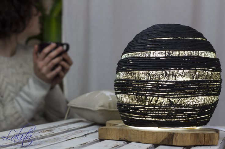 Around the Clock Lamp Table lamp, olive wood base and papier maché and string lampshade treated with black acrylic. Its soft light is ideal for creating a relaxing sense of comfort.