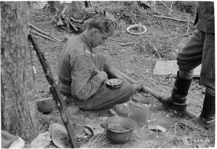 """A Finnish soldier loads a drum magazine for his KP-31 """"Suomi"""" submachine gun. The Suomi gave the Finnish army the upper hand in close quarters combat during the Winter War. By the Continuation War, with firsthand experience of its effectiveness, the Soviets had copied the model for their PPSh-41, which became a standard weapon for the Red Army. Over 6 million PPSh-41s were built in the Soviet Union during the Second World War."""