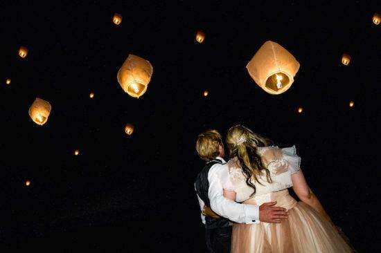 Un lâcher de lanternes magique féérique pour clôturer ce magnifique mariage de conte de fées Disney. Cette photo capture le couple des mariés dans un moment de compliucité.