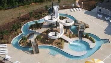 Explore the bridges of this built-in lazy river surrounding an enormous backyard swimming pool slide!