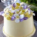 Elegant hand-crafted sugar petals in shades of yellow, white and purple top this simply frosted round cake.