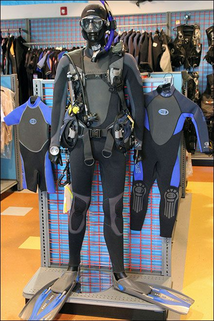 Male and female mannequins are Scuba Spokesmodels showing off the latest in rubber wear for undersea or fetish use. Snorkel-equipped, the girl mannequin is far less encumbered and farmore fashiona...