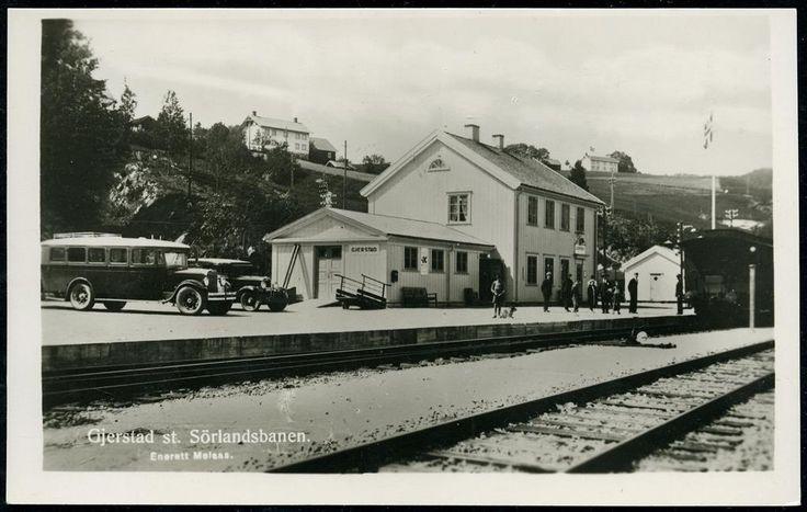 GJERSTAD ST. SÖRLANDSBANEN. Med stasjonsbygningen, folk på perrongen og fin buss som venter (Enerett Melaas