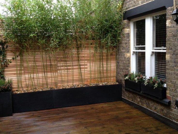 terrasse en bois composite décorée de bambous en bac rempli de galets