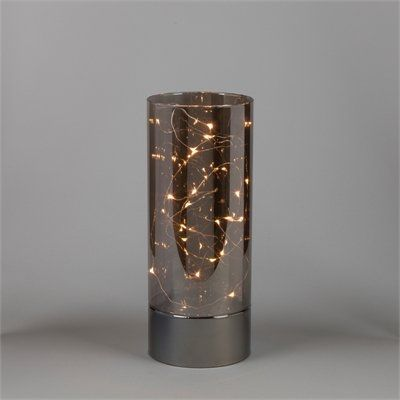 """A thin and bendable silver wire dotted with 15 warm white micro LED lights creates a celestial glow within this elegant smoked glass hurricane, which has a simple design that lets the lights take center stage. Use it in place of candles to add long-lasting holiday shimmer to any room. Requires 3 AA batteries (not included). 4"""" diameter, 10"""" tall. LED, wire, plastic, glass. Wipe with a soft dry cloth."""