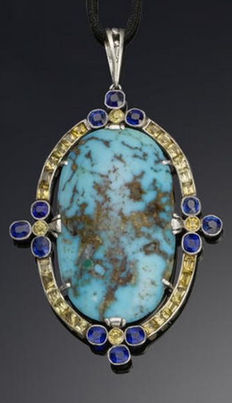 An art deco turquoise, sapphire and diamond pendant, by Fouquet, circa 1925 The large oval cabochon turquoise surrounded by rectangular-cut yellow sapphires and trefoils of circular-cut blue sapphires at the cardinal points, suspended from a woven silk cord with a turquoise and rose-cut diamond sliding plaque, mounted in platinum, signed G Fouquet and numbered, French assay marks, pendant length 8.8cm.