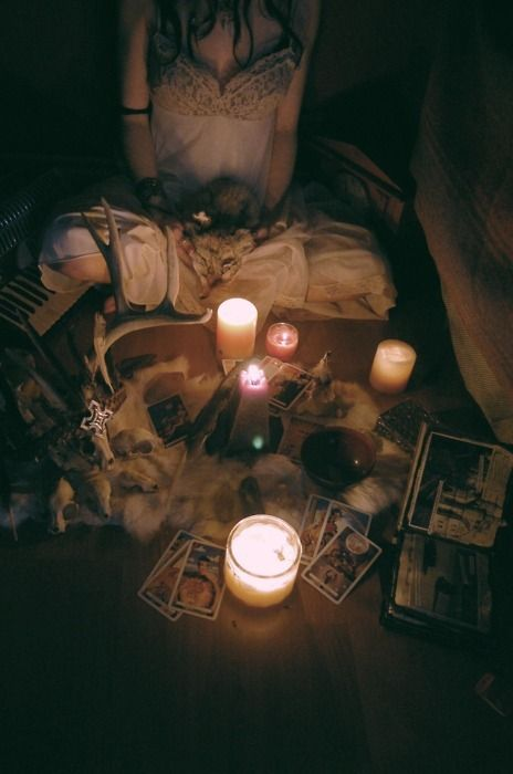 Entrancing setup with candles, furs, skulls, tarot cards, and more.