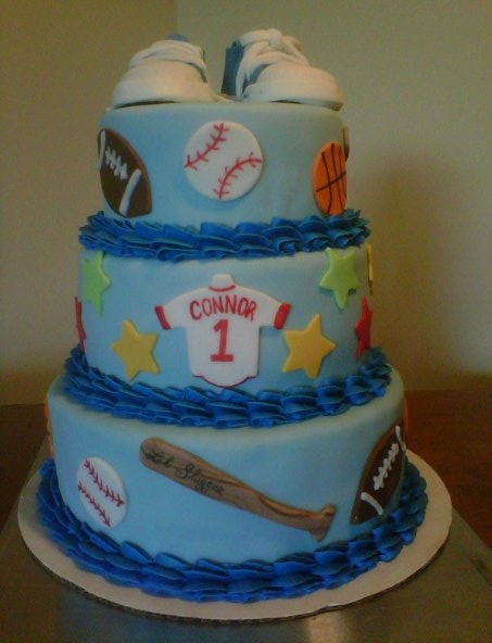 Sports theme 1st birthday cake. Covered in fondant with fondant decorations. Converse shoes are made from gumpaste.