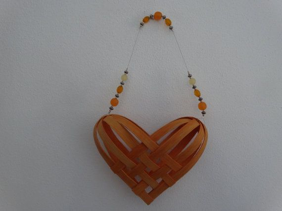 I call these little baskets braided hearts. I make them in lots of colors and use beads on the handles. They measure 11 from the top of the handle to the bottom tip of the heart. The heart itself is 6 long, 7 1/2 wide, and about 2 deep. This one is Light Peach. The beads are orange