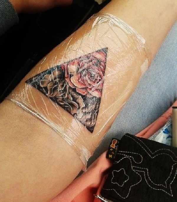 Beautiful rose inspired Triangle Glyph Tattoo. The roses are drawn within the triangle symbol. The black background is a stark contrast with the bright colors of the flowers.