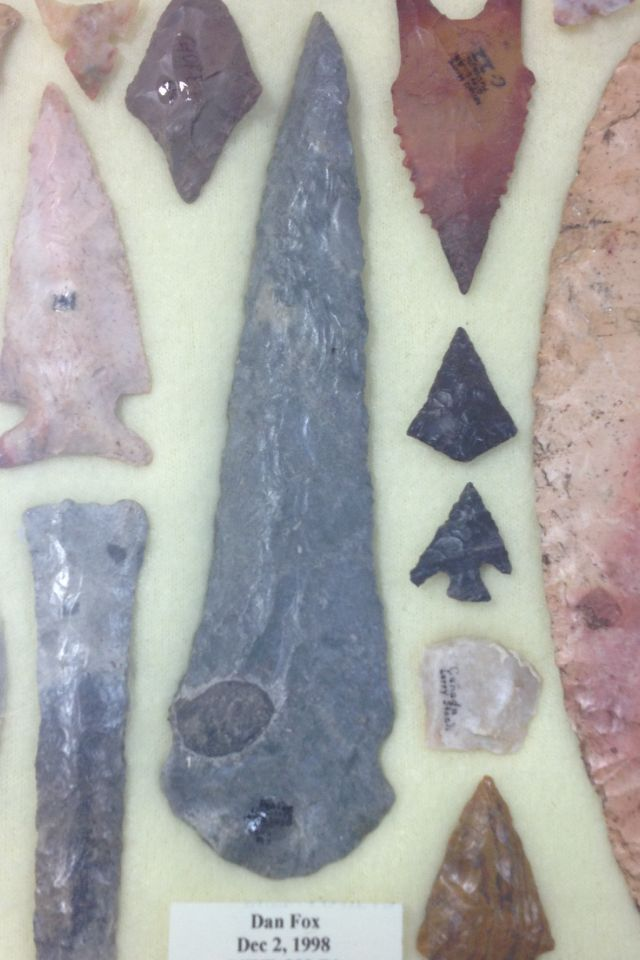 Center gray Sekans or Neosho River knife found in Kansas by Dan fox 5-3/4 inches longish. Beveled blade and shallow notches differentiate it from it contemporaries in late historic times such as the Harahey 4- way beveled knives.