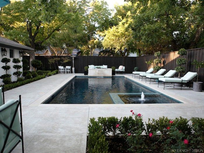 """Knight Moves: Pool and Patio Update. inset hot tub, gas firepit behind water feature, Lueders limestone coping, a concrete pool deck with a light acid wash, onyx quartz plaster, waterline tile is Noble Cobblestones 1"""" in the Ocean color"""