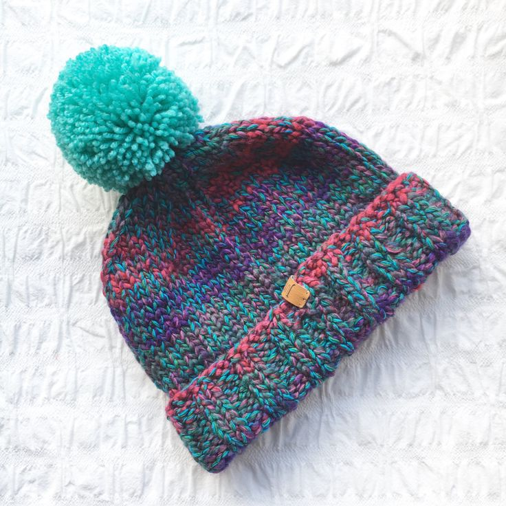 Hand-knitted bobble hat in multi colour purple, teal & pink yarn with teal bobble. Unisex fit. Knit in aran wool with a close stitch to give a nice neat fit. Finished with a faux leather Junkbox label & can be worn any way round. Colour may vary slightly as each hat is handknit from a different ball of yarn. 80% acrylic 20% wool