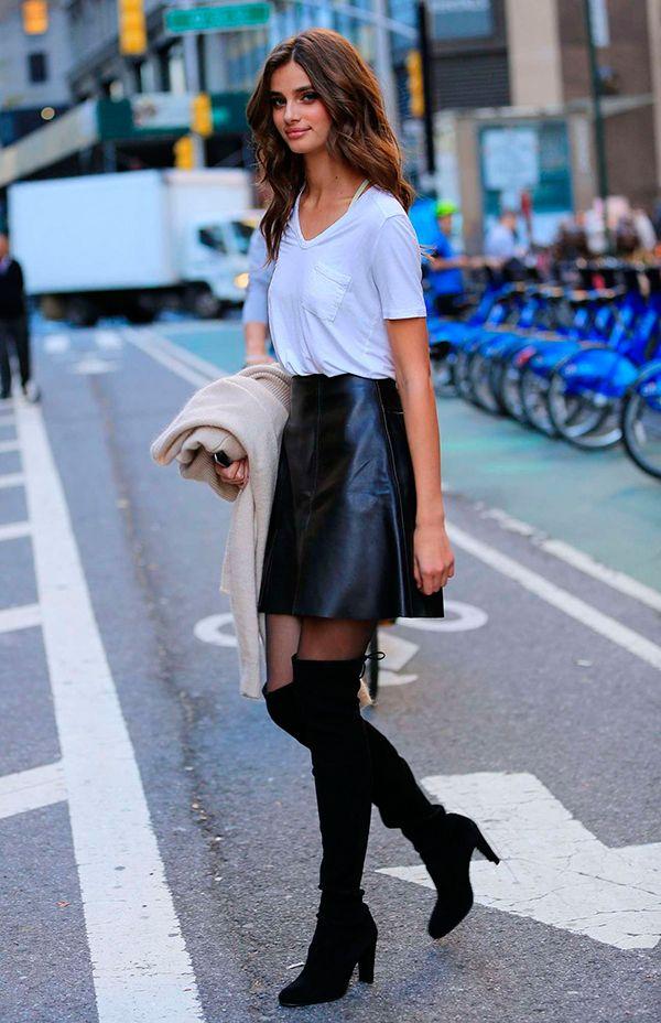 Taylor Hill usa look básico e sexy com t-shirt branca, saia preta de couro e botas over the knee pretas