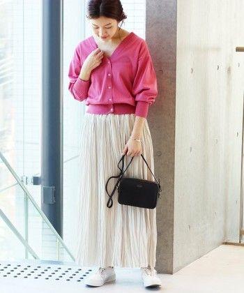 甘いチェリーピンクのカーディガンは、大人っぽい白のロングプリーツスカートと合わせてフェミニンに着こなして。足元はスニーカーでカジュアルダウンさせるのが◎