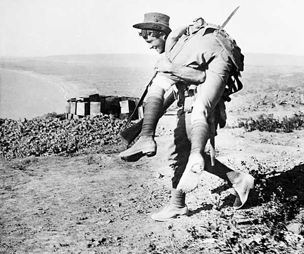 An Australian soldier carries a wounded comrade down from the ranges to a dressing station near North Beach at Gallipoli