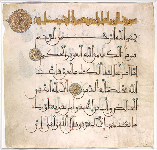 Leaf from a Qur'an manuscript, 13th-14th C. Attributed to Spain. This leaf comes from a magnificent two-volume Qur'an. The line of gold maghribi script at the top is the chapter, or sura, heading. The medallion in the left margin contains a brilliantly conceived two-layer vegetal pattern. In Qur'ans from the early Islamic period, such medallions took the form of palmettes, but by the time this Qur'an was copied, this pattern had assumed a preeminent position in the ornamental vocabulary.