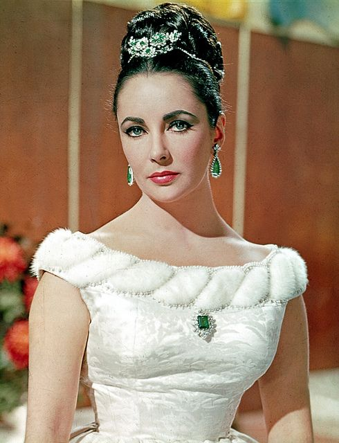 Elizabeth in the The V.I.P.s (1963) wearing her own diamond and emerald jewels including the brooch in her hair