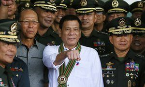 Rodrigo Duterte gestures as he poses with Philippine army officers during his visit to the army headquarters in Taguig, Philippines
