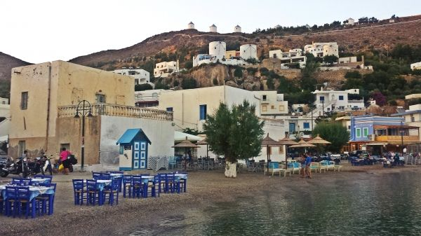 Pandeli beach: taverns on the beach and windmills on the hill