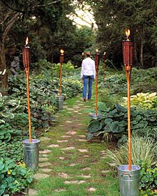 To anchor the torches, position flower buckets on level ground for stability. Hold one torch upright in each bucket, and fill the bucket with garden gravel to about 3 inches from the rim. The containers are then heavy enough to support the lit torches safely as they burn. Both the buckets and gravel are available at garden-supply centers; torches can be purchased at home-supply stores.