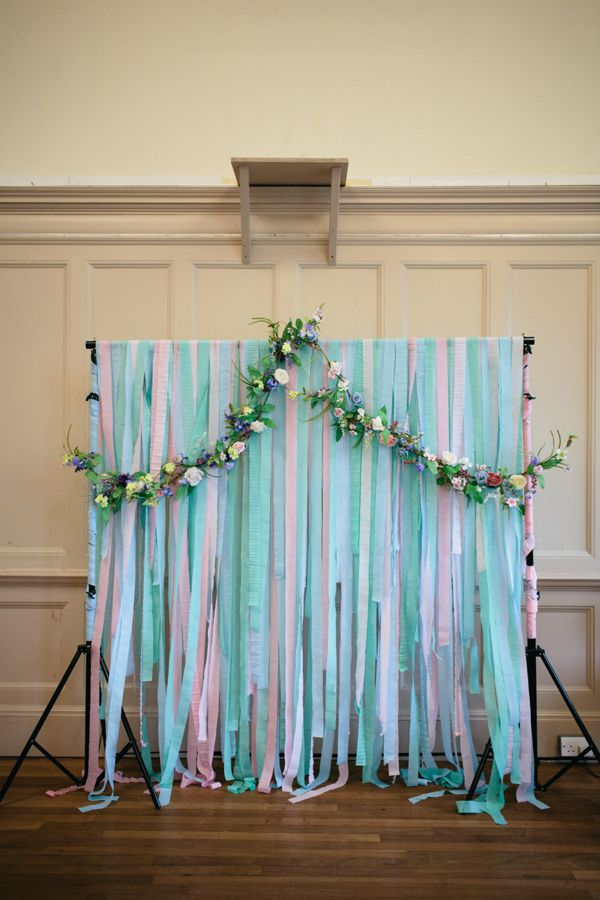 Humanist ceremony backdrop created using pastel colour streamers and a floral garland.  http://www.caroweiss.com/