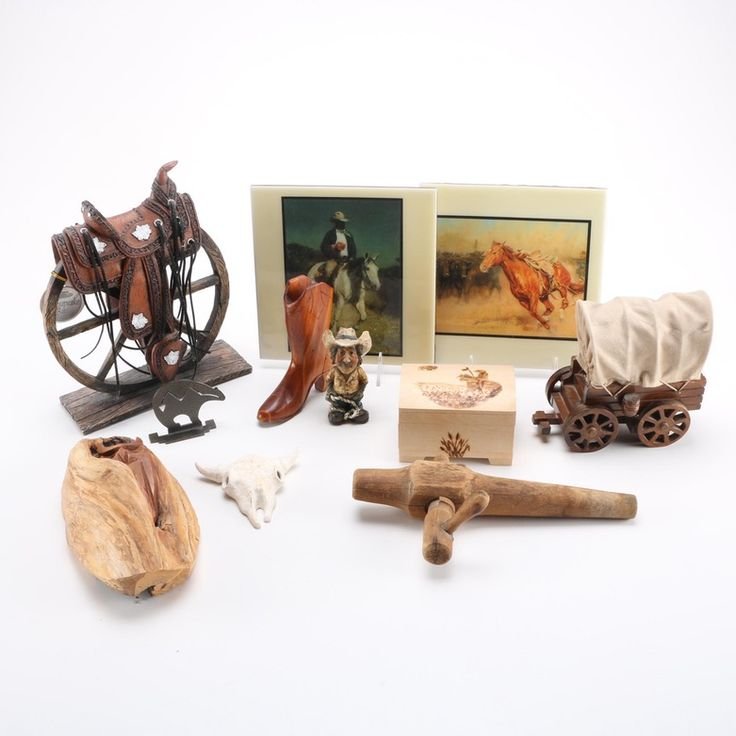 """A Southwestern decor collection. This collection of eleven items includes a musical covered stage coach and a resin western saddle resting over a wagon wheel. Also included is a wood boot that is signed to the underneath """"An Smith"""" also a wood burnt limited edition box by Paul and Christie Pronych."""
