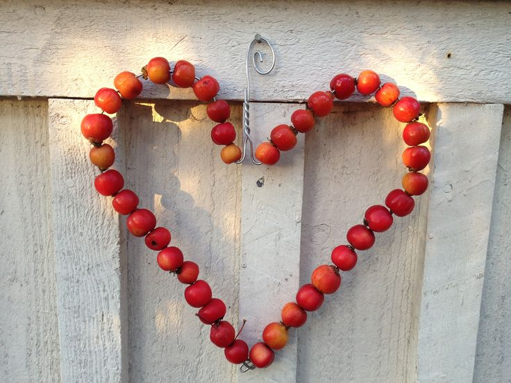 Heart made from clothes hanger. Decorated with a little red apples.