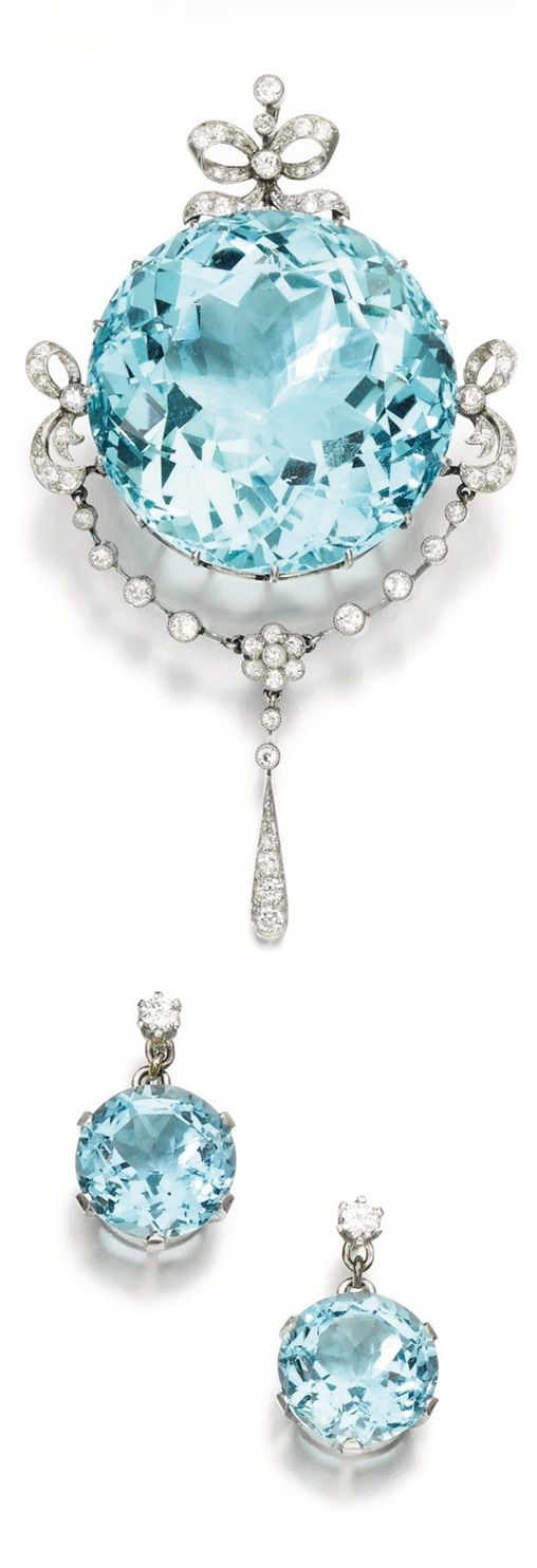 A Belle Epoque aquamarine and diamond demi parure, early 20th century composite. Comprising: a brooch claw-set with a circular-cut aquamarine, decorated with foliate and bow motifs set with circular-cut and rose diamonds; and a pair of earrings, each set with a circular-cut aquamarine, suspended from a brilliant-cut diamond, post fittings.