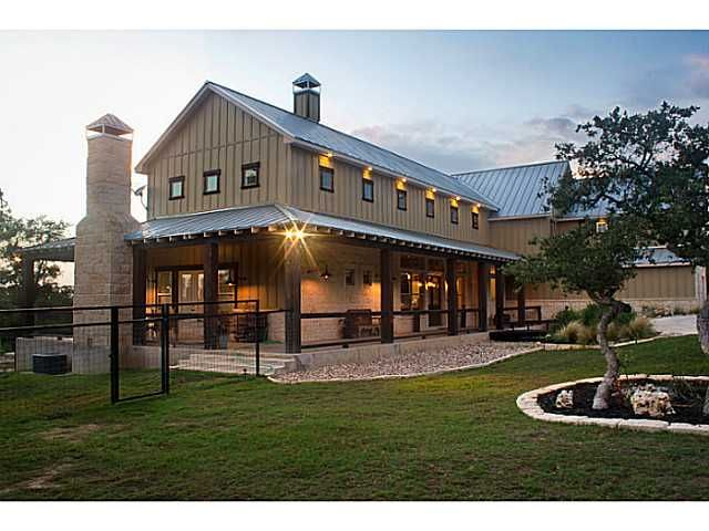 Pole building farmhouse. Metal roof. Board and batten. Wrap around porch. Outdoor fireplace.
