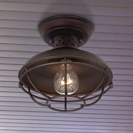 This outdoor ceiling light has a warm oil-rubbed bronze finish and vintage style metal cage.