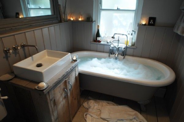 Wood-panelled bathroom has a deep stand-alone claw foot tub with handheld shower