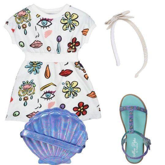 Un divertente abitino a maniche corte, sfondo bianco con fantasia colorata, di Moschino Kid è abbinato a sandali lilla con perline, piccola borsa a tracolla, a forma di conchiglia blu, cerchietto con fiocco di lamè, avorio, di Fendi.