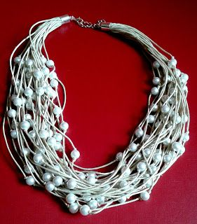 Naszyjnik wykonany ze sznurka woskowanego w kolorze ecru oraz białych, szklanych perełek.