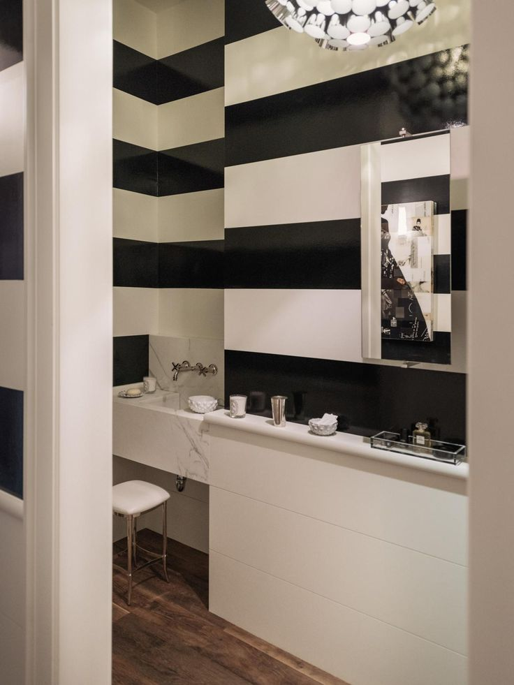 A sleek marble sink adds an elegant touch to the glossy black and white striped walls in this modern powder room. Hardwood flooring lends warmth to the space.