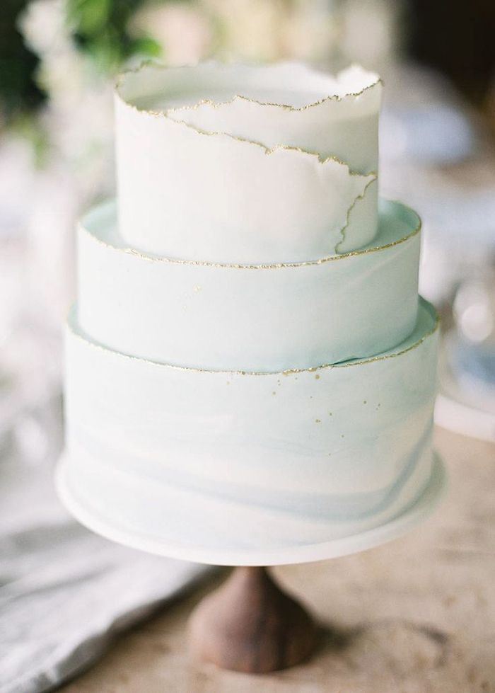 The softest sea foam green is mixed with white and wrapped around the cake like waves, with the edges gilded with gold.