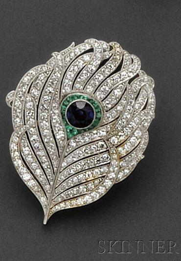 Art Deco platino engastada broche, diseñado como una pluma de pavo real, bisel-set con un zafiro, enmarcado por esmeraldas en forma de fantasía, más conjunto con melee solo corte diamantes