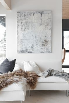 A white couch with blue + white pillows, a cashmere throw, and a fur blanket. Loving the piece of art too.