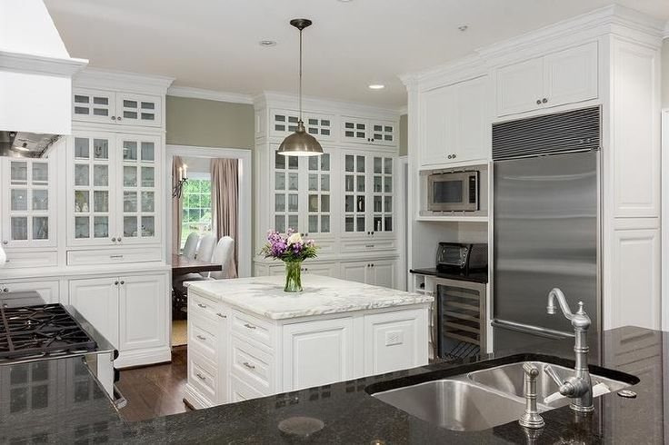 Small, efficient kitchen features an under cabinet fridge next to an integrated microwave stacked over toaster oven and a built-in wine rack next to a glass wine cooler.