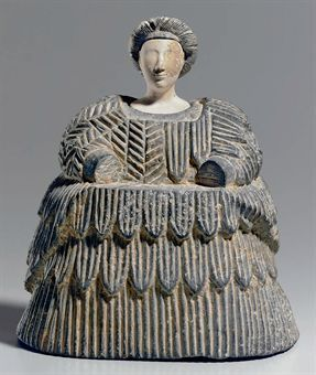 Bactrian composite stone female figure, late 3rd - early 2nd millennium B.C. The voluminous body formed of chlorite, the crinoline-like form of the skirt overlaid with layered kaunakes, flaring at the back toward the hem, the upper body patterned with hatching and chevron, tufts along the left shoulder, 18.4 cm high. Private collection