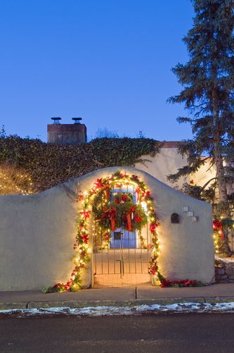 An abobe entrance decorated for Christmas in Santa Fe, New Mexico.