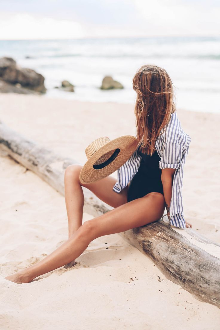 Jess Ann Kirby wearing a striped button down and black one piece