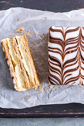 Topped with sweet frosting and pipped chocolate, this mille feuille recipe is the ultimate afternoon tea treat. | Tesco
