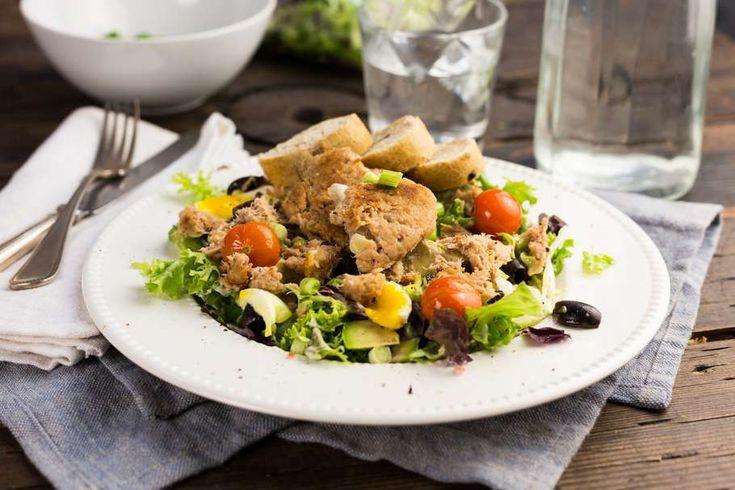 Recept voor maaltijdsalade voor 4 personen. Met zout, boter, peper, tonijn uit blik, zwarte olijven, bosui, cherrytomaat, brood, ei, paneermeel, mayonaise, slamelange, avocado en caesar sladressing