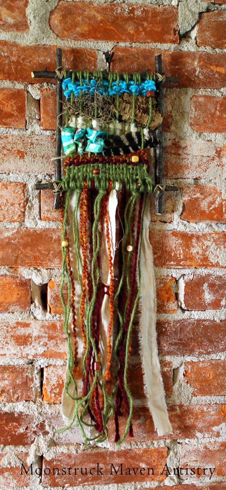 Hand made yarn, fabric, bark & feather weaving on a branches.