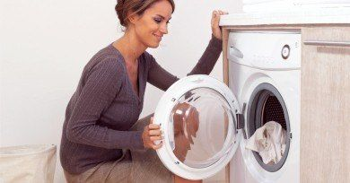 WomanKneelingbyWasher | How to Whiten White Clothes That Are Yellowing