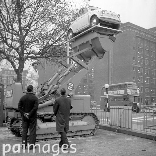 1962. A Fiat 500 City car riding high in Kensington, London, on the bucket of a 10-ton Fiat FL8 tractor shovel. Anyone who buys a similar 6,300 tractor, or Fiat equipment of the same value during the Public Works and Municipal Services Exhibition will be given the car free