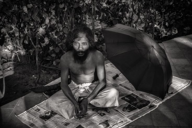 Black and white portrait of a yogi resting in the grounds of a temple complex by the banks of the Hooghly River in Kolkata, India