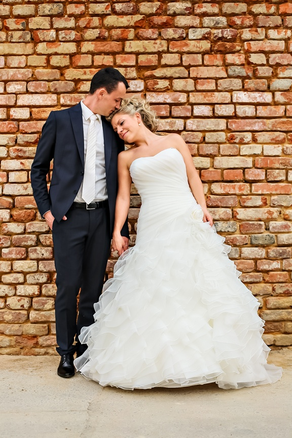 wedding couple pose by brick wall