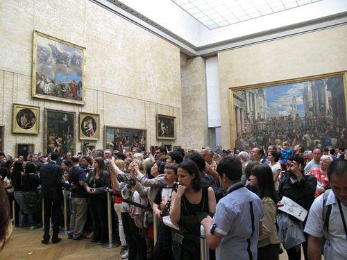 Het Louvre, met links het dringen voor de Mona Lisa en rechts Paolo Veronese's De bruiloft te Kana